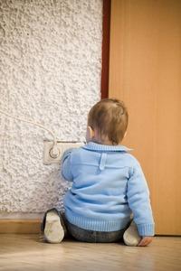 Kindersicherung, Kind spielt an Steckdosen, Vorsicht Strom
